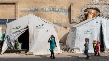 Displaced Syrian children walk past their tents in a stadium turned into a makeshift refugee shelter in Idlib on Thursday.