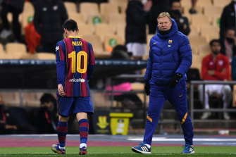 Lionel Messi heads off the pitch after being shown a red card, as his coach Ronald Koeman looks on.