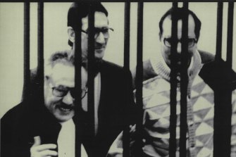 "Luciano Leggio (left), the reputed ""boss of bosses"" of Italian Cosa Nostra, smiles from behind the bars during he big mafia trials in Sicily in 1986."