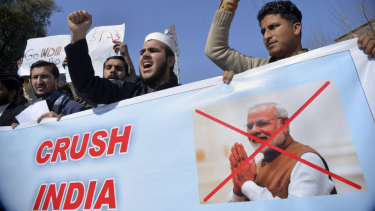 Pakistanis rally behind a banner showing Indian Prime Minister Narendra Modi in Peshawar on Wednesday.
