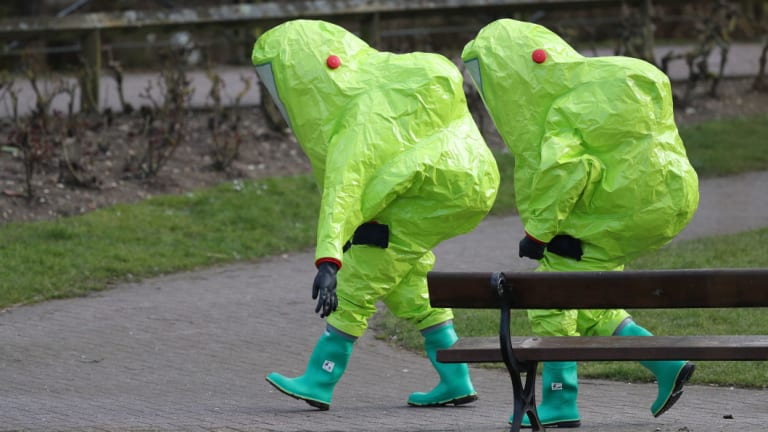 Personnel in hazmat suits walk away after securing the covering on a bench in the Maltings shopping centre where former Russian double agent Sergei Skripal and his daughter Yulia were found critically ill.
