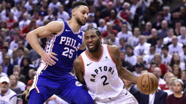 Kawhi Leonard drives to the net as Ben Simmons defends.