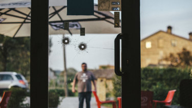 Bullet holes on the door of the H7 pub, where the gunman had worked until he was fired in October, in Macerata.