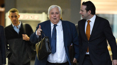 Businessman Clive Palmer (centre) leaves the District Court in Brisbane on July 23.