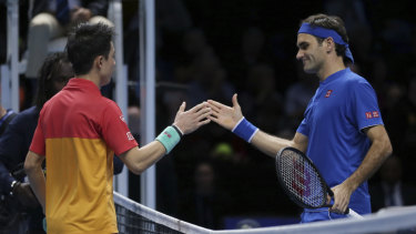 Give him a hand: Kei Nishikori shakes hands with Roger Federer after Nishikori beat his idol.