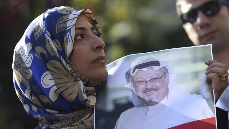 Holding a picture of missing Saudi writer Jamal Khashoggi, Tawakkol Karman, the Nobel Peace Prize laureate for 2011, talks to members of the media near the Saudi Arabia consulate in Istanbul on Friday.