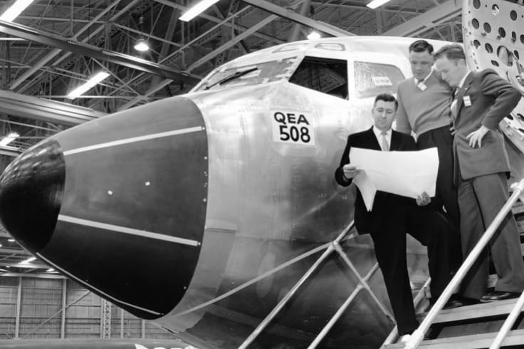 Brian Van de Water (holding plans) with VH-EBH on the production line at Seattle, 1961.