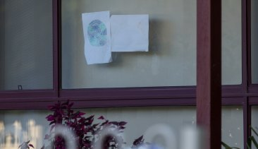 A child's drawing in the window of the Perinovic's home.