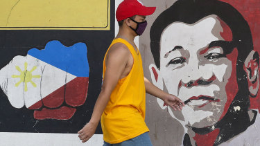 A man wearing a protective mask walks past an image of Philippine President Rodrigo Duterte in Manila.
