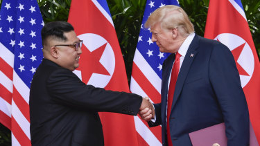 """In love"": North Korea leader Kim Jong-un and US President Donald Trump shake hands at the conclusion of their meetings in Singapore in June."