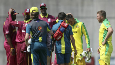 Players gather around Usman Khawaja (second right) after he was struck on the helmet.