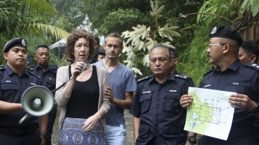 Meabh Quoirin, second left, the mother of a missing British girl Nora Anne Quoirin, speaks to police officers as father Sebastien Quoirin, centre, stands beside her, in Seremban, Negeri Sembilan, Malaysia.