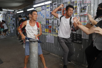 Pro-China supporters, in white, fight with pro-democracy protesters at the Kowloon Bay district in Hong Kong on Saturday.