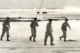 An army search party equipped with two-way radio look for Harold Holt on Cheviot Beach.