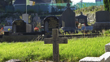 An Irish flag flies over the graves in a cemetery in Carrickcarnan, Ireland, near Northern Ireland, where the Brexit deal runs into trouble.