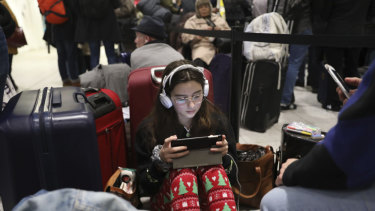 Passengers at Gatwick airport settle down to wait for their flights following the delays and cancellations brought on by drone sightings near the airfield, in London.