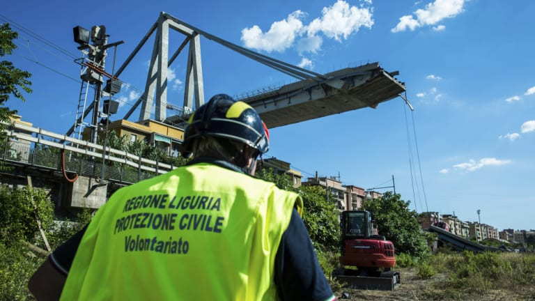 A worker inspects the the area around the collapsed Morandi highway bridge, in Genoa.