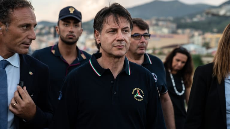 Giuseppe Conte, Italy's prime minister, centre, arrives at the site of the collapsed Morandi motorway bridge in Genoa.