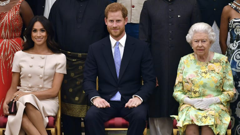 The Queen, Prince Harry and Meghan, Duchess of Sussex, pose for a group photo at the Queen's Young Leaders Awards Ceremony at Buckingham Palace.