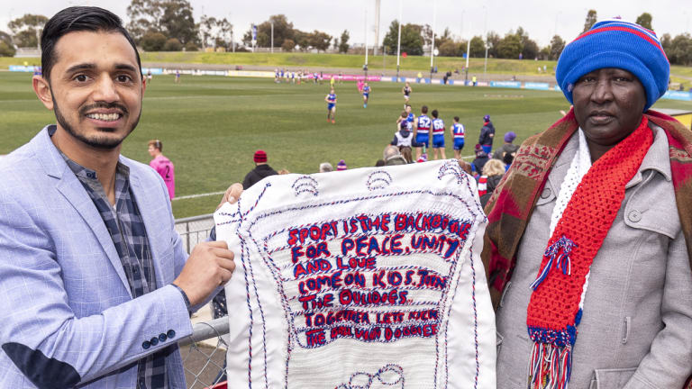Kashuf Bouns (left) and Agostina Nyibol hold a knitted banner made by Agostina.