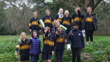 Bentleigh West Primary students, with Dr Kavitha Chinathamby from RMIT, front right, throw GPS-tracked bottles into Dandenong Creek as part of the Litter Trackers program.
