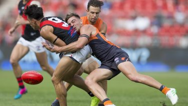 Welcome back: Stephen Coniglio dispossesses former GWS teammate Dylan Shiel, now with Essendon.