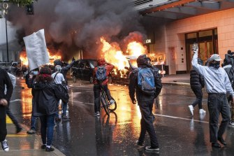 People set fire to vehicles during a protest in Seattle on Saturday.