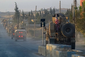 US military vehicles travel down a main road in north-east Syria on October 7.