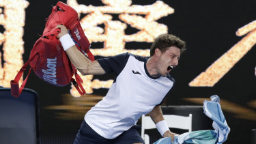 Spain's Pablo Carreno Busta throws his bag in frustration after losing his fourth round match to Japan's Kei Nishikori.