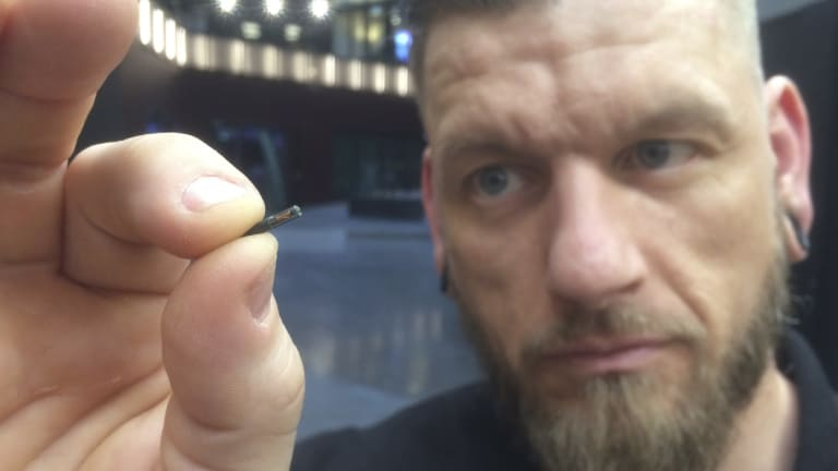 """Self-described """"body hacker"""" Jowan Osterlund from Biohax Sweden, holds a small microchip implant, similar to those implanted into workers in Sweden."""