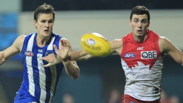 Hot pursuit: Scott Thompson of the Kangaroos and Tom McCartin of the Swans chase down the ball.