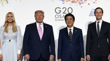 President Donald Trump poses for a photo with Japanese Prime Minister Shinzo Abe and Ivanka Trump and senior advisor Jared Kushner ahead of a meeting on the sidelines of the G20 summit in Osaka.