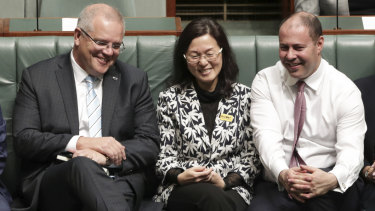 Liberal Gladys Liu is flanked by Prime Minister Scott Morrison and Treasurer Josh Frydenberg during a division in the House of Representatives.