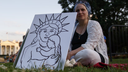 Susan Kane of Rockville, Md., sits on the grass in front of the White House