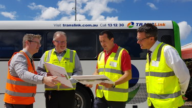 Transdev head of engineering Marc Cleave, Transdev Queensland head of business Mark McKenzie, Capalaba MP Don Brown and TransLink CEO Matt Longland look at mock-ups of the e-bus at the Capalaba depot.