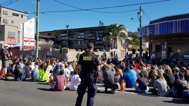 Protesters sat in silence for seven minutes outside the Kangaroo Point hotel where 120 refugees are being kept, to mark seven years of offshore detention.