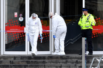 Forensic officers examine the scene of the stabbing at Manchester's Arndale Centre.
