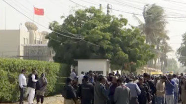 Security officials gather outside the compound of the Chinese Consulate following an attack on Friday.