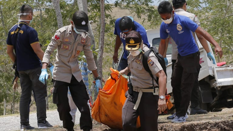 Rescue teams carry the body of a tsunami victim during a mass burial in Palu, Central Sulawesi, Indonesia, on Monday.