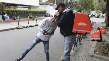 Venezuelan bicycle courier Luis Tarre, 60, kisses the head of his 20-year-old son Raul as they wait for Rappi delivery orders. A large number of food couriers in Bogota, Colombia, have basically become full-time workers, and MPs are considering regulations to boost protection for the workers.