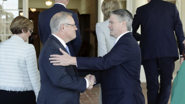 Prime Minister Scott Morrison greets Finance Minister and Dutton backer Mathias Cormann during the swearing-in of the new ministry on Tuesday morning.