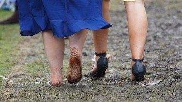 Barefoot racegoers brave the mud.