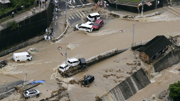 Roads are covered in mud waters after a landslide caused by heavy rains in Aki, Hiroshima prefecture, south-western Japan, on Saturday.