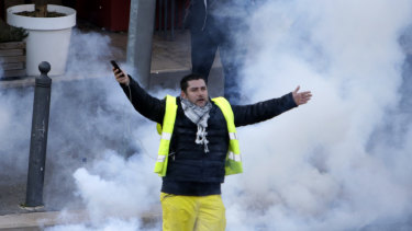A yellow vest demonstrator gestures through tear gas during a protest on Saturday in Marseille, southern France.