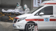 Medical staff transfer patients to hospital in Wuhan.