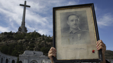 A visitor holds a portrait of former Spanish dictator Francisco Franco at the Valley of the Fallen mausoleum.