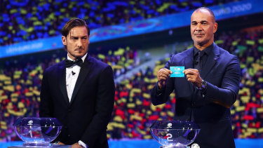 Ruud Gullit, former Netherlands player, draws France from the pot during the UEFA Euro 2020 draw in Bucharest.