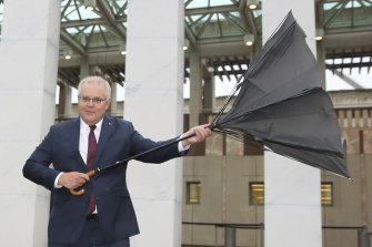 Prime Minister Scott Morrison carrying an umbrella arrives for breakfast television interviews on the front lawn of Parliament House on Wednesday.
