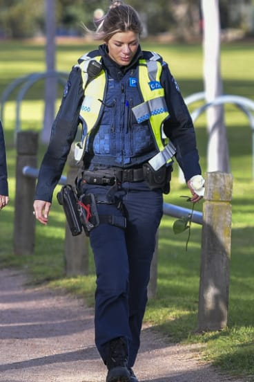 A female police officer holds a white rose to place near where Eurydice Dixon was killed.