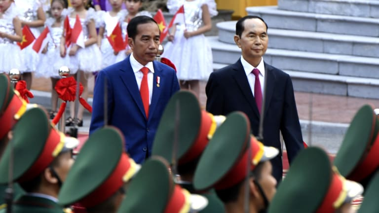 """Indonesian President Joko """"Jokowi"""" Widodo, left, and Vietnamese counterpart Tran Dai Quang review the troops on Tuesday."""